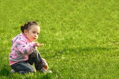 Il bambino un fiore sentente l'odore in un'erba verde Immagini Stock Libere da Diritti