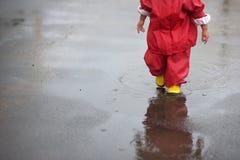 Il bambino in un impermeabile cammina nella pioggia e nei giochi in uno stagno Fotografie Stock Libere da Diritti