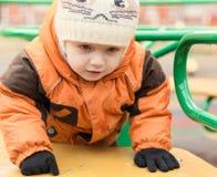 Il bambino in un rivestimento ed in un cappuccio caldo, ad un campo da giuoco in autunno da Fotografia Stock Libera da Diritti