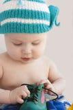Il bambino in una protezione gioca con un un pattino verde Fotografie Stock Libere da Diritti