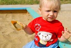 Il bambino in una sabbiera immagine stock