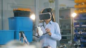 Il bambino in una stanza del laboratorio tiene un giocattolo bianco mentre indossa gli occhiali di protezione di VR video d archivio