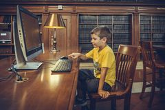 Il bambino utilizza il computer nella biblioteca pubblica indicativa di New York Fotografie Stock