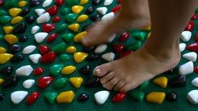 Il bambino va a piedi nudi su una stuoia ortopedica del piede stock footage