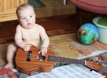 Il bambino vago impara giocare le ukulele a casa Immagine Stock