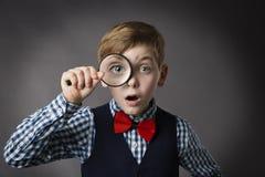 Il bambino vede attraverso la lente d'ingrandimento, lente della lente dell'occhio del bambino