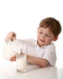 Il bambino versa il latte Fotografia Stock Libera da Diritti