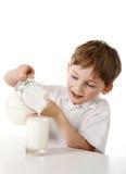 Il bambino versa il latte Fotografia Stock