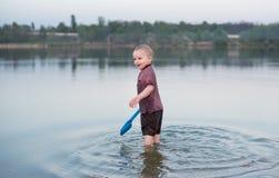 Il bambino in vestiti sta nel lago immagine stock