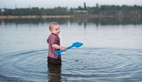 Il bambino in vestiti sta nel lago immagini stock