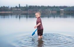 Il bambino in vestiti sta nel lago fotografia stock libera da diritti