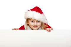 Il bambino vestito come Babbo Natale tiene il segno in bianco dell'annuncio Fotografie Stock Libere da Diritti