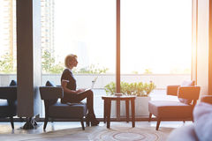 Il banchiere femminile sicuro sta sedendosi con il NET-libro in caffetteria durante la pausa al lavoro Immagine Stock Libera da Diritti