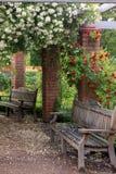 Il banco del giardino di Upsala con le rose parcheggia in Svezia fotografie stock
