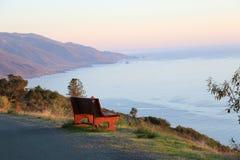Il banco di legno arancio trascura la linea costiera di Big Sur, CA Fotografie Stock Libere da Diritti