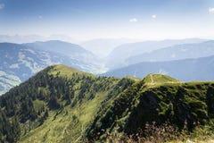 Il banco di legno con le montagne idilliache delle alpi dell'estate abbellisce in Austria Fotografie Stock Libere da Diritti