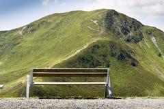 Il banco di legno con le montagne idilliache delle alpi dell'estate abbellisce in Austria Fotografia Stock Libera da Diritti