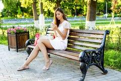 Il banco di seduta della bella ragazza, il vestito rosa castana, stile di vita di modo con il vostro telefono scrive un messaggio Fotografie Stock Libere da Diritti