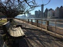 Il banco in una zona del parco con l'orizzonte di Manhattan ai precedenti immagini stock