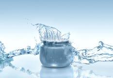 Il barattolo blu di crema d'idratazione con grande spruzzata e l'acqua scorrono intorno sui precedenti del blu di pendenza Fotografie Stock Libere da Diritti