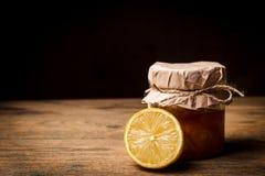 Il barattolo con inceppamento arancio sopra wodden il fondo Fotografie Stock