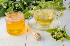 Il barattolo del miele del tiglio, del cappuccio del tè del tiglio e del ramo con il tiglio fiorisce Immagine Stock