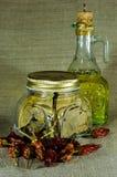 Il barattolo della foglia, del peperoncino e della bottiglia di alloro con l'olio di girasole Fotografie Stock