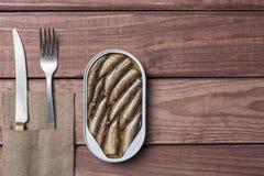 Il barattolo di latta degli spratti pesca, sardine con il coltello e forcella sulla tavola di legno Vista superiore e spazio libe Fotografia Stock Libera da Diritti
