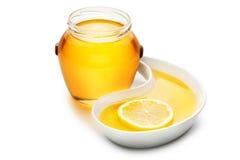 Il barattolo di miele accanto ad una fetta di limone in uno strappo ha modellato il vassoio, iso Fotografia Stock Libera da Diritti