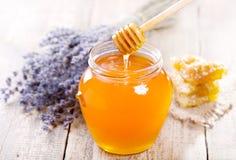 Il barattolo di miele con il favo e il lavander fiorisce Fotografia Stock