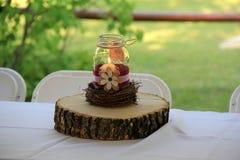 Il barattolo di muratore e di legno esamina in controluce il centro sul tavolo a nozze Fotografia Stock Libera da Diritti