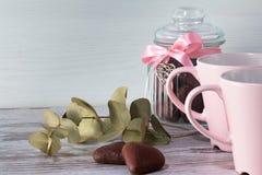 Il barattolo per i biscotti e due biscotti nella forma di cuore mettono sul fondo grigio chiaro Due tazze rosa per tè Fotografie Stock Libere da Diritti