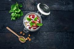Il barattolo pieno dei muesli, il yogurt, i lamponi, dadi sul nero, ha bruciato la tavola di legno Alimento casalingo dei cereali Fotografie Stock