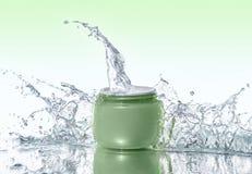 Il barattolo verde dei soggiorni crema d'idratazione sui precedenti dell'acqua con acqua spruzza intorno Fotografia Stock