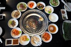 Il barbecue coreano, con l'insieme della tavola della griglia e della verdura Immagini Stock