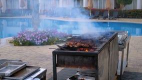 Il barbecue del pollo ? cucinato su una grande griglia da un cuoco all'hotel dallo stagno con acqua blu Egypt video d archivio