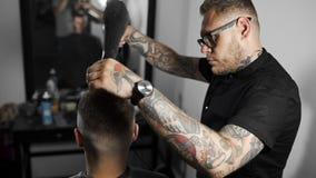 Il barbiere asciuga i capelli e fa i capelli che disegnano per il cliente al negozio di barbiere, taglio di capelli del ` s dell' archivi video