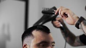Il barbiere asciuga i capelli e fa i capelli che disegnano per il cliente al negozio di barbiere, taglio di capelli del ` s dell' stock footage