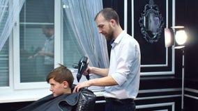 Il barbiere asciuga il ragazzo dei capelli con hairdryer in parrucchiere stock footage