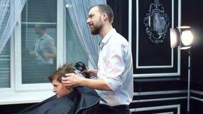 Il barbiere asciuga il ragazzo dei capelli con hairdryer in parrucchiere video d archivio