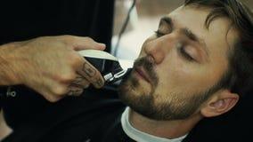 Il barbiere barbuto di talento sta sistemando la barba del suo cliente in un capo nero dei capelli di taglio nel parrucchiere Sta video d archivio