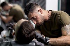Il barbiere bello in guanti neri sistema una barba dell'uomo alla moda ad un parrucchiere immagini stock