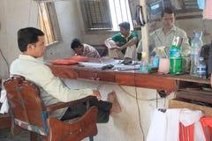 Il barbiere cambogiano senza lavoro esamina lo specchio Fotografia Stock Libera da Diritti