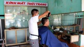 Il barbiere che ha un taglio di capelli per l'ospite fotografie stock libere da diritti