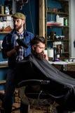 Il barbiere con hairdryer lavora all'acconciatura per il fondo barbuto del parrucchiere dell'uomo Cliente barbuto dei pantaloni a immagini stock