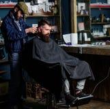 Il barbiere con la tosatrice lavora a taglio di capelli del fondo barbuto del parrucchiere del tipo Cliente dei pantaloni a vita  immagini stock libere da diritti