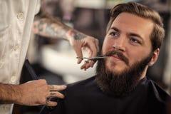 Il barbiere dell'uomo con le forbici ha tagliato i baffi fotografia stock