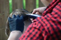 Il barbiere dell'uomo sta tagliando i suoi capelli con un ragazzo della macchina da scrivere immagini stock