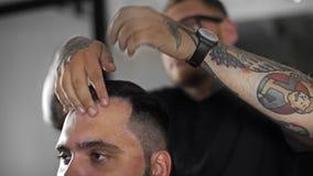 Il barbiere di Tattoed fa i capelli che disegnano con il gel di capelli per il cliente dopo il taglio di capelli al negozio di ba stock footage