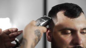 Il barbiere di Tattoed fa il taglio di capelli per il cliente al negozio di barbiere usando il hairclipper, il taglio di capelli  archivi video